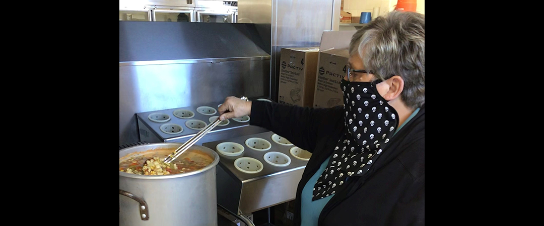 Cafe staff stirs pot of vegetable soup