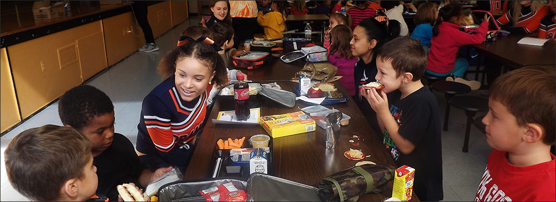High school students eating lunch with elementary students.