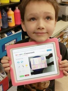 Student holding iPad with artwork displayed on screen.