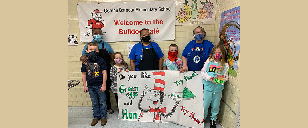 Elementary Schools pose with cafe staff as they are serving Green Eggs and Ham to celebrate Read Across America activities